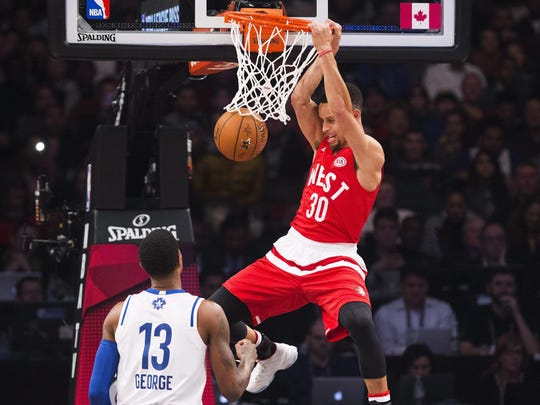 Western Conference's Stephen Curry, of the Golden State Warriors, (30) slam dunks the ball past Eastern Conference's Paul George, of the Indiana Pacers (13) during the first half of the NBA all-star basketball game, Sunday, Feb. 14, 2016 in Toronto. (Mark Blinch/The Canadian Press via AP) MANDATORY CREDIT