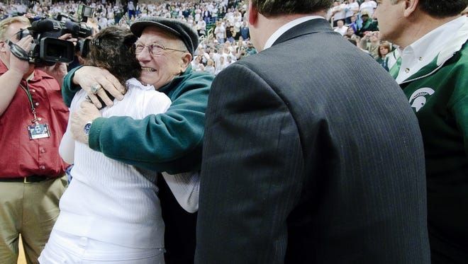 Carl Izzo (second from left) hugs his daugher-in-law Lupe Izzo (from left) as her husband MSU Men's Basketball Head Coach Tom Izzo and Steve Mariucci look on after MSU claimed a share of the Big Ten title by defeating Michigan Sunday March 7, 2010 in East  Lansing.  KEVIN W. FOWLER PHOTO