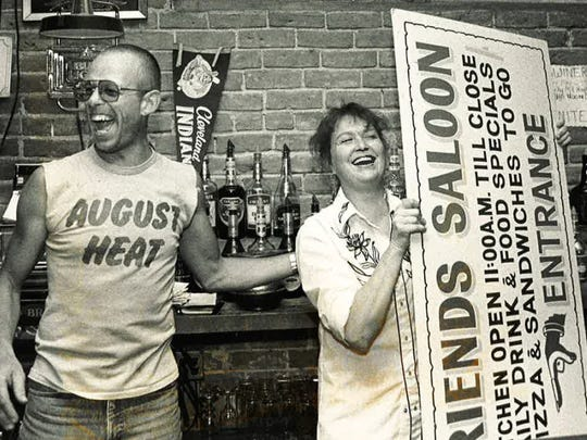 Paco Montanri and Susan Unger, part-time employees at Friends Saloon, share a laugh after Unger bought a sign at a going-out-of-business auction at the bar, which closed in 1988.