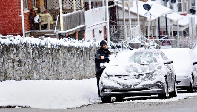 Damion Kamarauskas, of York City, brushes the snow off of his car near Farquhar Park in York City, Tuesday, Jan. 30, 2018. Dawn J. Sagert photo