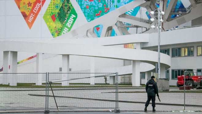 A security guard patrols an entry gate to the Olympic Park in Sochi, Russia, on Jan. 22.