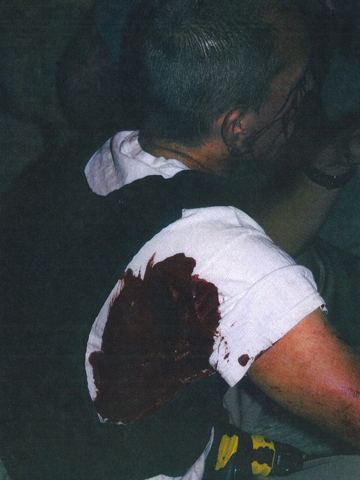 Dane Norem bleeds from a stab wound to his back in a crime scene photo from October 2012.