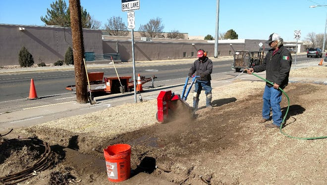 Workers for New Mexico State University's Facilities and Services Department trench holes into the yards of student homes on Espina Street to install a subsurface irrigation system to reduce the amount of water being wasted by traditional sprinklers.