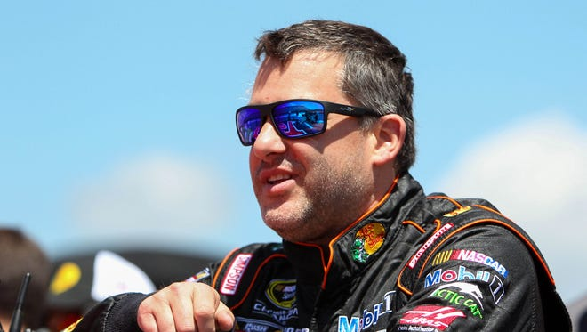 Tony Stewart leans on his car prior to the Axalta 'We Paint Winners' 400 at Pocono Raceway on June 6.
