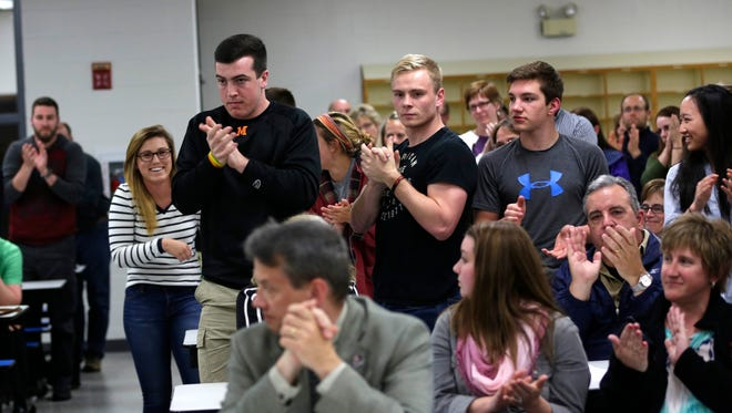 Students, parents and teachers give a standing ovation after testimony from a student  during a highly attended board meeting on Wednesday, May 11, 2016, about the resignation of Marshfield High School Principal Steve Sukawaty .