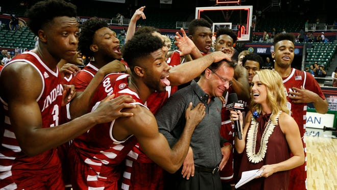 Indiana Hoosiers celebrate behind coach Tom Crean as he is being interviewed by ESPN after the game against the Kansas Jayhawks at the Stan Sheriff Center. Indiana defeats Kansas 103-99 in overtime.