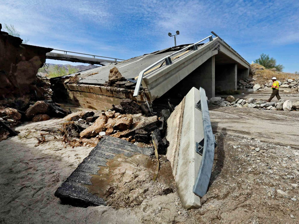 A worker walks near a washed-out bridge near the town of Desert Center, along Interstate 10 in Southern California. All traffic along one of the major highways connecting California and Arizona was blocked indefinitely when the bridge over a desert w