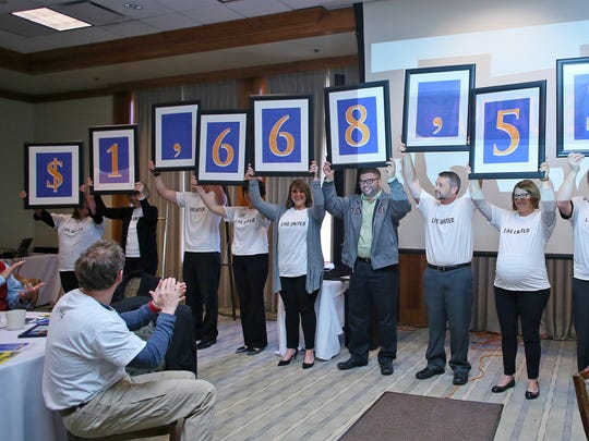 Fundraising campaign volunteers hold up the amount raised by the United Way of Licking County during their annual meeting and recognition breakfast held Thursday at The Virtues Golf Club.