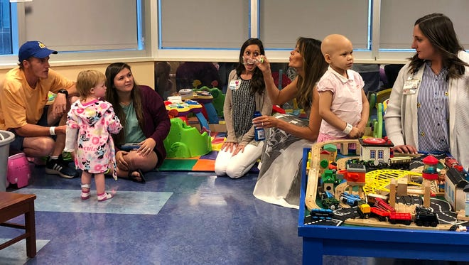 """First lady Melania Trump blows bubbles in a playroom with children during a visit to Monroe Carell Jr. Children's Hospital at Vanderbilt in Nashville, Tenn., Tuesday, July 24, 2018. The first lady was promoting her """"Be Best"""" campaign to help children. (AP Photo/Darlene Superville)"""