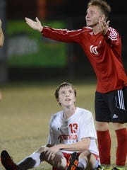 An Edgewood player pleads his case to a referee during a high school soccer game.