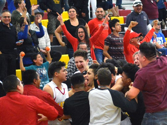 """Centennial players and fans swarm around Centennial's Cesar Molina after he hits the game winning shot against Los Lunas Saturday afternoon at """"The Nest."""""""