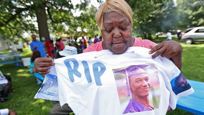 """Helen Yeakey on July 12, 2015, holds a T-shirt depicting several family members who have died in gun violence, including her grandson, who she buried the day before this """"Stop the Violence"""" picnic in Denver Park, Indianapolis."""