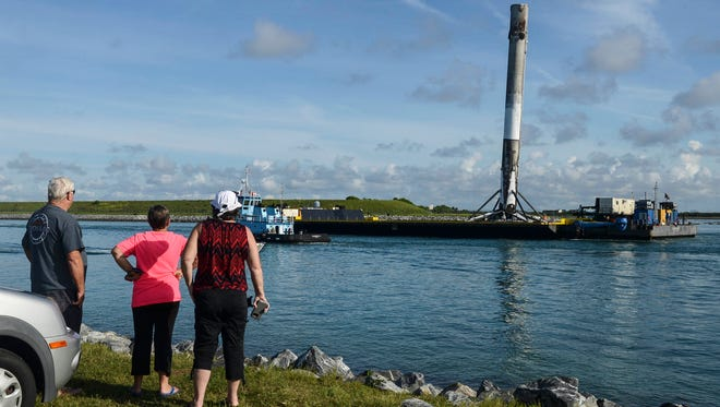 Spectators watch as a SpaceX Falcon 9 first stage is brought back into Port Canaveral Thursday morning aboard the Of Course I Still Love You.