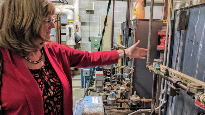 Millis Superintendent of School Nancy Gustafson, shown examining rusty pipes at the old Clyde Brown School, announced that she is retiring, effective Dec. 1.