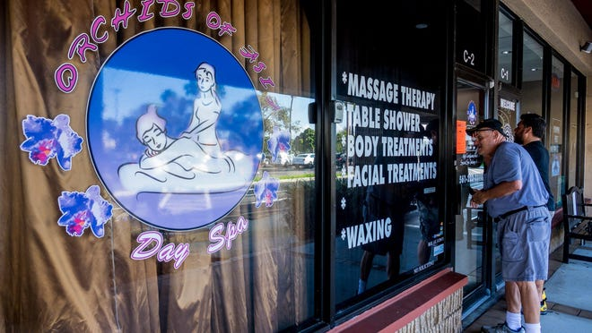 Onlookers try to peek inside the Orchids of Asia day spa in Jupiter after authorities shut it down in February 2019.