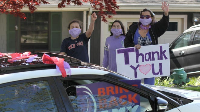 Amy Mullen waves to a motorist during a rolling rally in May after the longtime Tiverton teacher was fired from her position. A judge ruled Friday that Mullen's First Amendment rights were violated and she can retain her job.