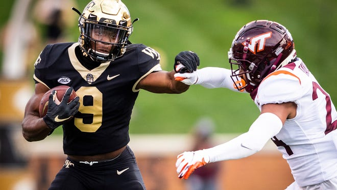 Wake Forest sophomore running back Kenneth Walker III (9) breaks a tackle by Virginia Tech cornerback Devin Taylor (24) during an NCAA college football game Saturday, Oct. 24, 2020, in Winston-Salem, N.C. (Andrew Dye/The Winston-Salem Journal via AP)