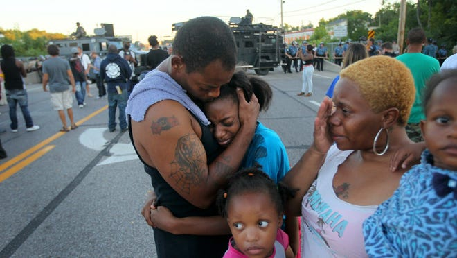 Terrell Williams El embraces his daughter Sharell, 9, next to his wife, Shamika Williams, and daughters Tamika, 6, and Shanell, 2, in Ferguson, Mo. on Wednesday after he confronted police during a protest.