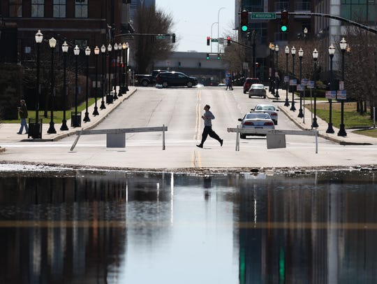 A jogger passed flood waters at the intersection of