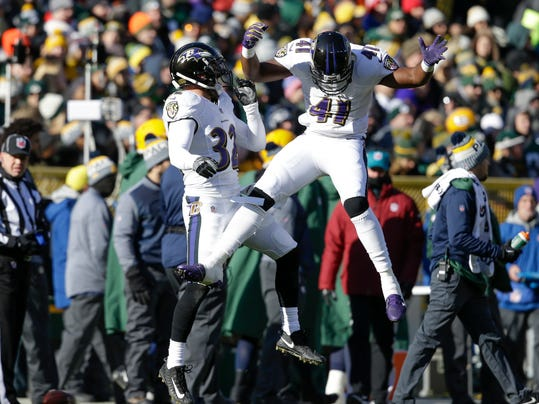 Baltimore Ravens' Eric Weddle celebrates his interception with teammate Anthony Levine (41) during the first half of an NFL football game against the Green Bay Packers Sunday, Nov. 19, 2017, in Green Bay, Wis. (AP Photo/Jeffrey Phelps)