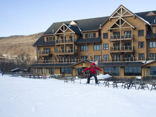 A snowboarder glides in front of the Jay Peak Tram Haus Lodge in 2012. Vermont Timber Works crafted the hotel's balconies and entryway.