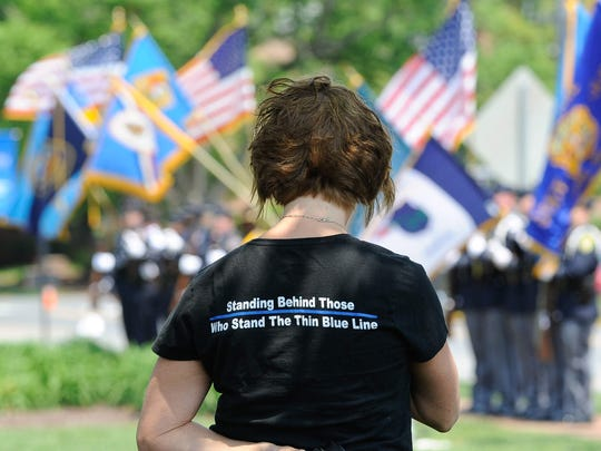 A woman wears a shirt supporting the police at the Fraternal Order of Police memorial at Legislative Hall for officers wounded or killed in the line of duty.