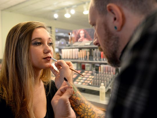 Christopher Endsley, a colorist at Douglas J Salon and Day Spa, applies lipstick on Karleigh Madaj.