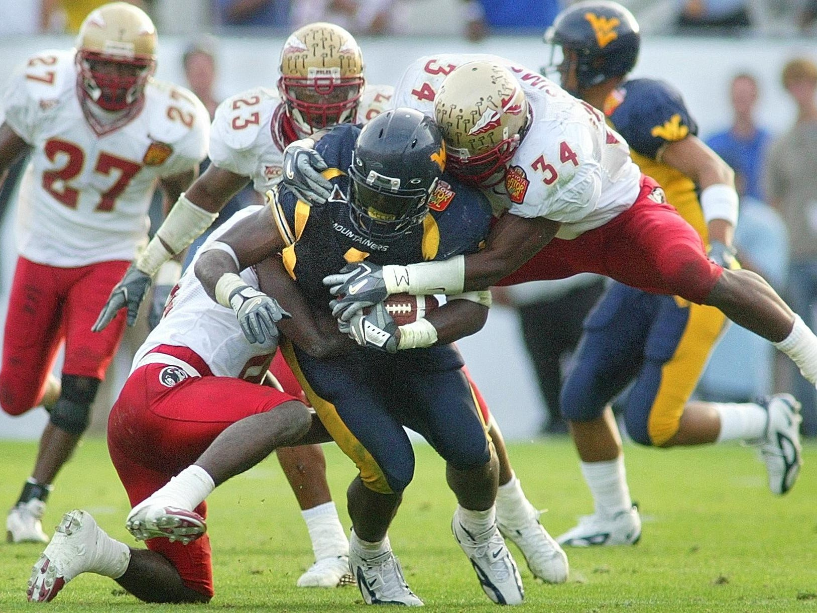 FSU's Bryant McFadden (8) and Ernie Sims (34) nail West Virginia running back Kay-Jay Harris on a run during a 2004 game.