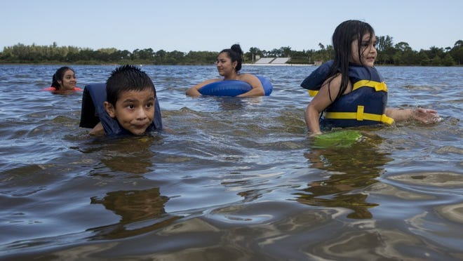 From left: Elizabeth Garcia, 11, Aries Ayala, 6, Paulina Garcia, 16, and Rosa Garcia, 4, all of Naples, swim together in Lake Avalon at Sugden Regional Park on June 23, 2016 in Naples, Florida. (Nicole Raucheisen/Staff)