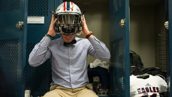 COURTNEY SACCO/CALLER-TIMES Veterans Memorial's Austin Gustafson puts on his helmet while packing his gear in the locker room before the team leaves for their first game Friday.