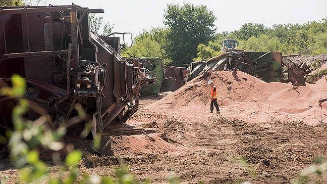 A worker walks among overturned rail cars and piles of grain spilled during a train derailment Thursday morning. The 104-car Texas Pacifico train was eastbound carrying grain that had been loaded in Miles, Texas. A dozen cars were destroyed or damaged in the incident, no injuries were reported. - photo by Ken Grimm/Standard-Times