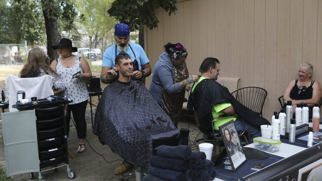Photos by Andreas Fuhrmann/Record Searchlight De Ja' Vu Salon employees give haircuts to job seekers Friday at the Job Preparedness Resource Fair.