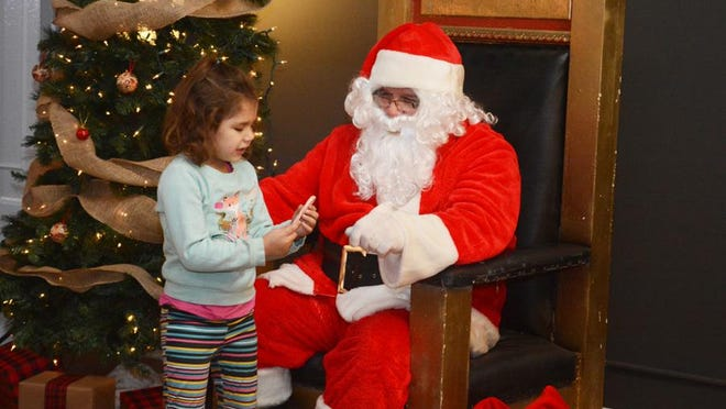 Santa Claus shares a Christmas treat with Radiance Griewahn, 4, of Adrian on Dec. 7, 2018, during First Fridays at the Gallery of Shops in Adrian. The Gallery of Shops won't be hosting Santa this year due to the pandemic but will have an online presentation instead.