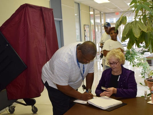 Robert Steward (left) signs the book before casting his vote at the Pineville Municipal Building as polling commissioner Linda Dubroc looks on.