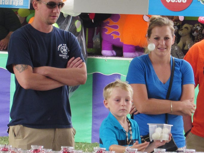 Brayden Vanderpoel tries to drop a ping pong ball into a glass jar for prizes during Sunday's Schuyler County Italian American Festival in Watkins Glen. Looking on are Mason and Danielle Jones, of Rock Stream.