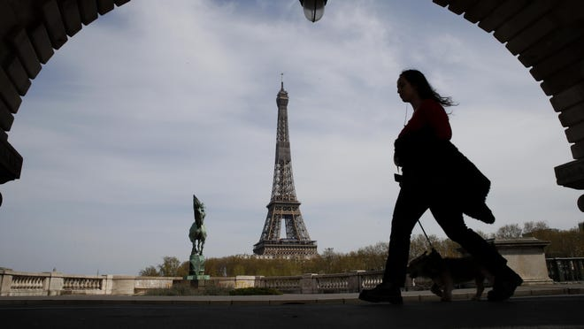 FILE - In this Tuesday, April 7, 2020 file photo, a woman walks her dog on a Paris bridge, with the Eiffel tower in background, during a nationwide confinement to counter the COVID-19. The European Union announced Tuesday, June 30, 2020 that it will reopen its borders to travelers from 14 countries, but most Americans have been refused entry for at least another two weeks due to soaring coronavirus infections in the U.S.