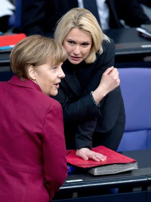 German Chancellor Angela Merkel, left, and German Minister of Family Affairs Manuela Schwesig talk during a session of Parliament in Berlin on  Friday, March 6, 2015.