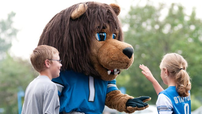 Aug 2, 2014; Detroit, MI, USA; Detroit Lions mascot Roary high fives fans during training camp at the Lions training facility.