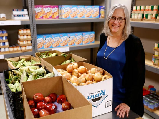 Marci Rafdal, administrator for the Des Moines Community Action Agency, shows off the supplies in its food pantry.
