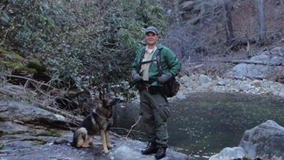 Jason Crisp, a law enforcement ranger with the U.S. Forest Service in Asheville, is seen here with his K-9 Maros. Both were killed by a murder suspect in March 2014.