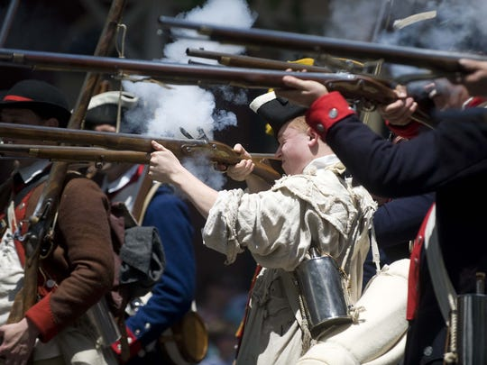 File: Members of the New Jersey Volunteers exchange volley fire with the British Army on Kings Highway in Haddonfield near the Indian King Tavern Museum during the re-enactment of the two-day encampment that took place on June 18 and 19, 1778.