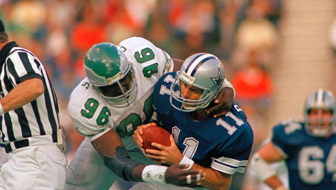 Dallas Cowboys quarterback Danny White (11), right, is sacked by Philadelphia Eagles Clyde Simmons for a 22-yard loss during fourth quarter action in Philadelphia, Oct. 26, 1987.