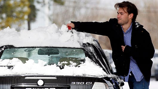A motorist wipes off the snow from the roof of his car in Starkville, Miss., Thursday, Feb. 26, 2015. Snow accumulations from Wednesday evening piled high on all vehicles parked outdoors. Hazardous driving conditions continued over much of northern Mississippi Thursday as the remnants of a storm system lingered.