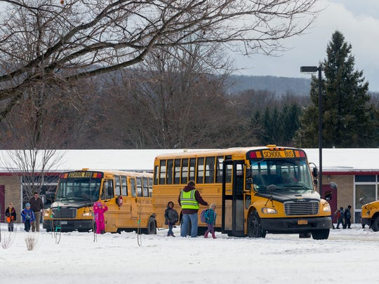 Staff and bus drivers escort children to the buses Feb. 17 outside Caroline Elementary School. Extended water test results now show many sources of water in the school have elevated lead levels.