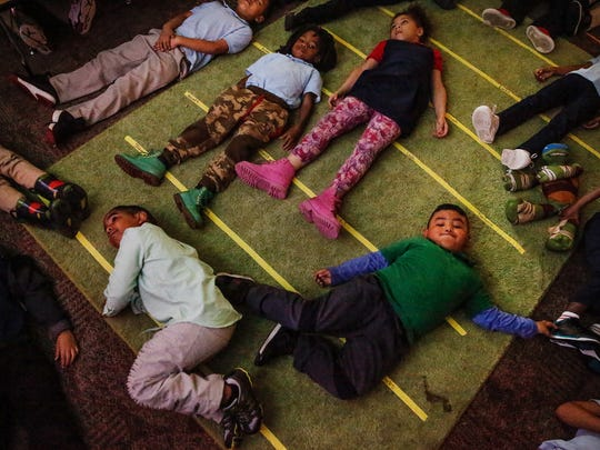 """After breakfast, inside the class room of Clarence Farrington School 61 kindergarten teacher Alyssa Collin, students gather on a green carpet to practice yoga for 10-minutes. """"Why do we do yoga in the morning?"""" asked Collin on Thursday, May 4, 2017. """"Because it makes us calm down,"""" the kids replied. """"This helps us get ready to focus on today and we will be?"""" said Collin. """"The best!"""" the kids yelled."""
