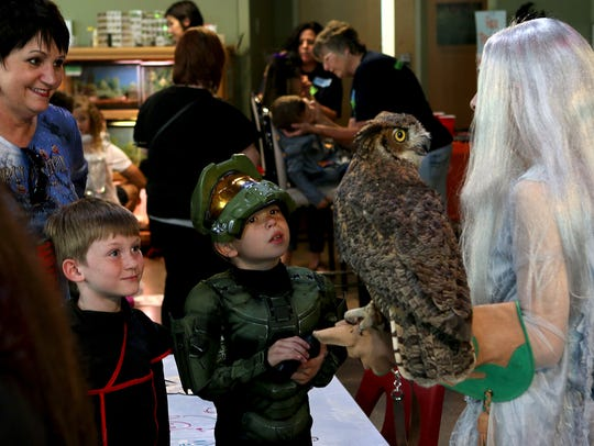 In this file photo, several children learn about an owl from Wild Bird Rescue volunteers at River Bend Nature Center's Not So Scary Halloween. The nonprofit puts HE laundry detergent on its Christmas wish list.
