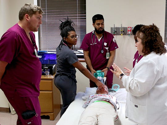 Tammy Kurszewski, clinical chair of the respiratory care program at Midwestern State University, right, talks with a team of nursing, radiology and respiratory care students about the scenario Friday morning in Bridwell Hall.