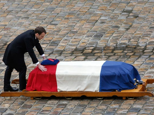 French President Emmanuel Macron leans at the coffin