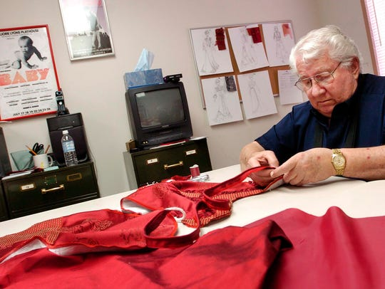 """FILE: Bob Buseick, president of the Red River Repertory Theatre, works on some of the costumes for the upcoming """"The Little Foxes"""" in 2006."""