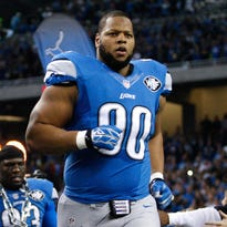 Detroit defensive tackle Ndamukong Suh runs onto the field before a game at Ford Field. Suh is looking to become the highest paid defensive player in the league.